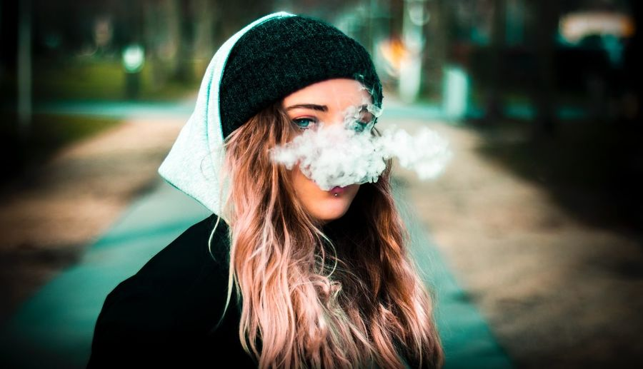 Portrait of young woman smoking outdoors