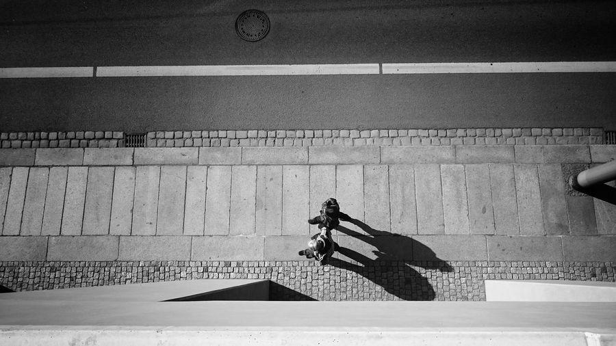 High angle view of men walking on sidewalk