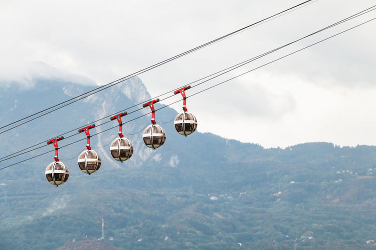 Overhead cable cars hanging against sky