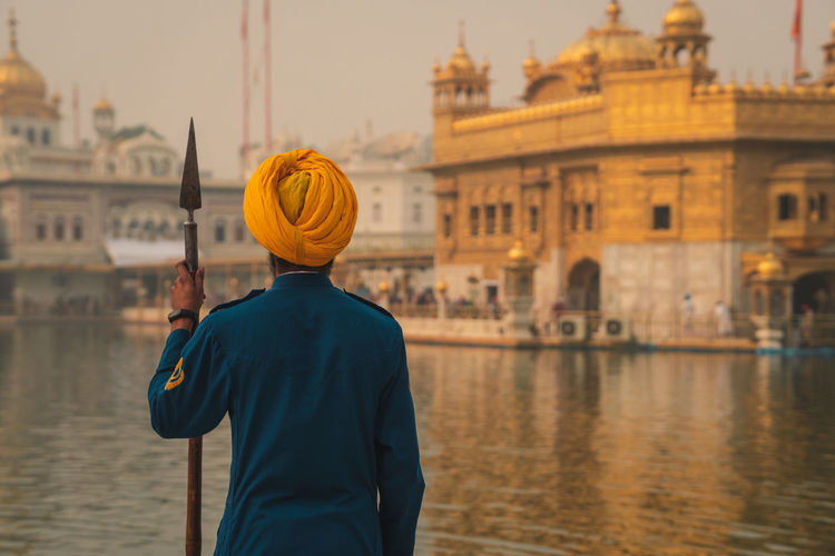 Rear view of man standing in city against the golden temple