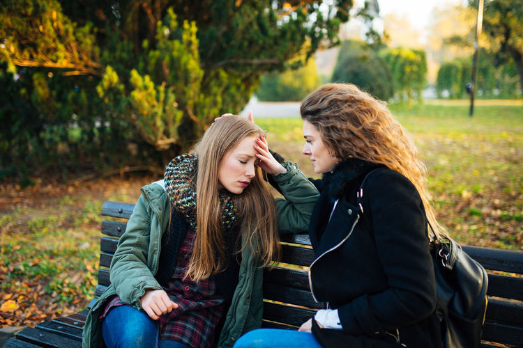 Worried Woman Talking To Friend While Sitting In Park During Autumn