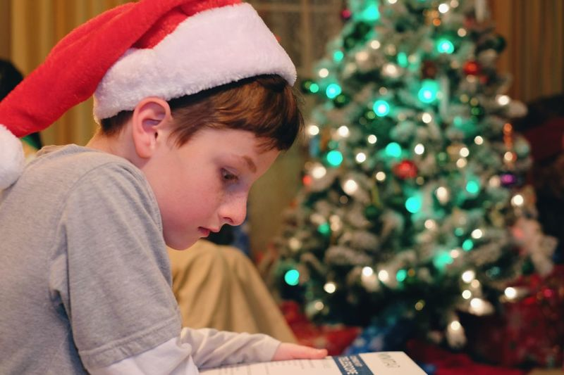 Close-up of boy reading book with illuminated christmas tree in background