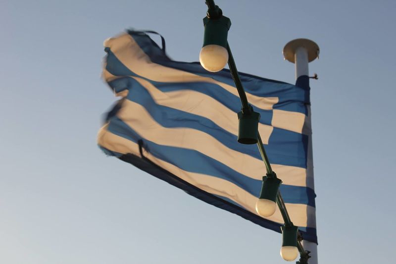 Low angle view of greek flag against sky