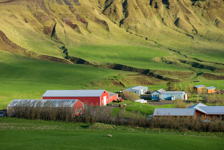 Scenic view of agricultural field by houses and mountain