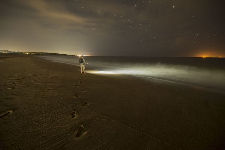 Man standing at beach against sky at night