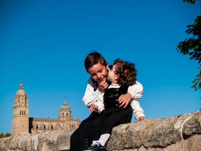 Cute boy kissing brother sitting on wall against historic building