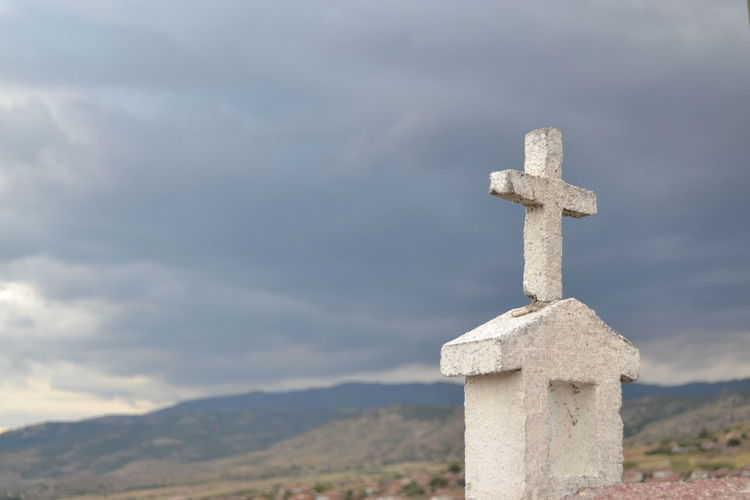 Close-Up Of Cross In Cemetery Against Sky