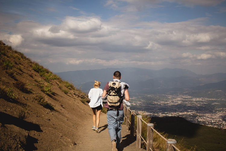 Rear view of man and woman walking on mountain against sky