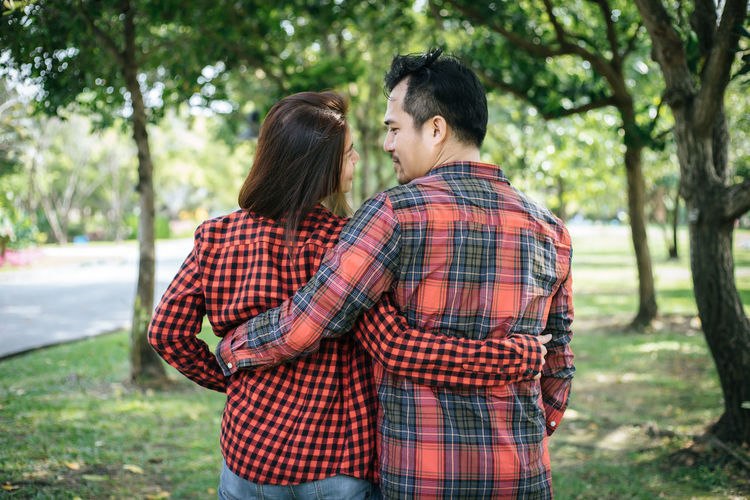 Adult Bonding Care Casual Clothing Couple - Relationship Emotion Focus On Foreground Hairstyle Heterosexual Couple Love Men Outdoors Plant Positive Emotion Romance Standing Togetherness Tree Two People Women Young Adult Young Men Young Women