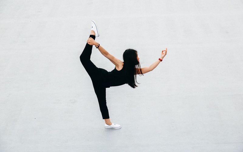 Full length of woman doing yoga against white background