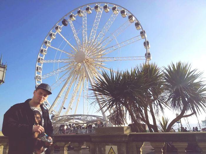 Man Standing Against Ferris Wheel In City