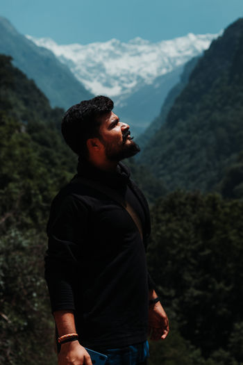 Young man looking away while standing against mountains