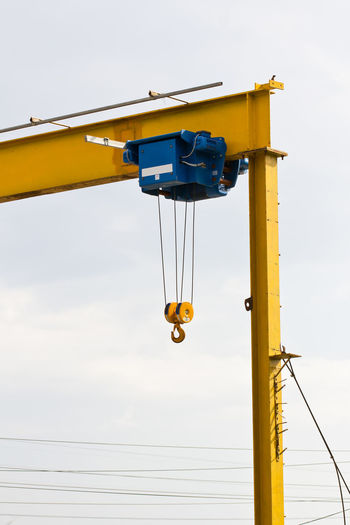 Low angle view of yellow crane against sky