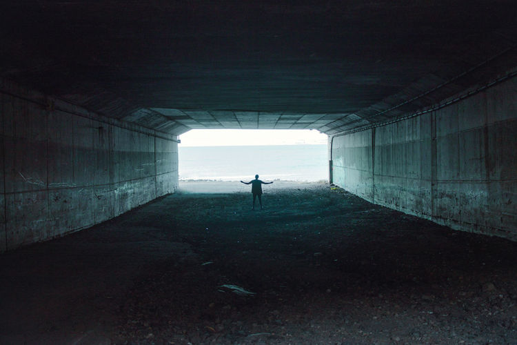 Rear View Of Silhouette Person Standing In Tunnel Against Sea