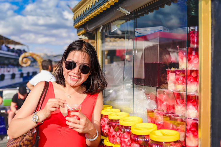 Portrait of woman wearing sunglasses holding food while standing in market