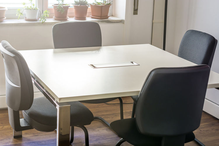 Empty chairs and table in office