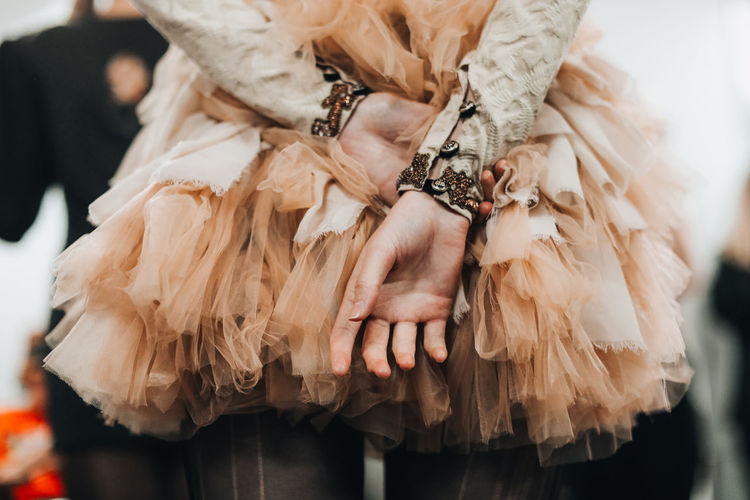 Women's hands on the background of a lush beige organza skirt