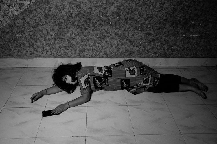 High angle view of girl lying on tiled floor at home