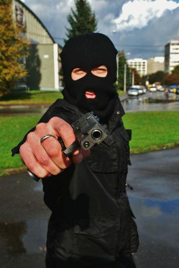 Portrait of burglar in mask aiming gun on street