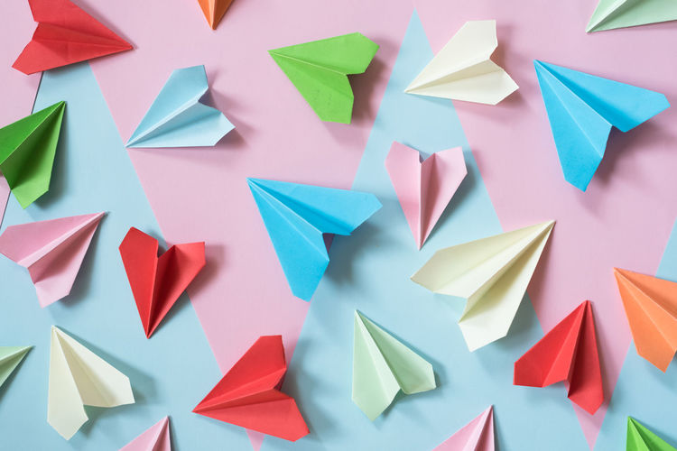 High angle view of multi colored paper airplane on table