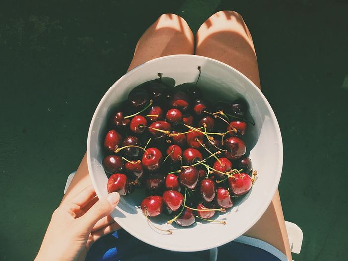 Directly above shot of woman sitting with cherry bowl