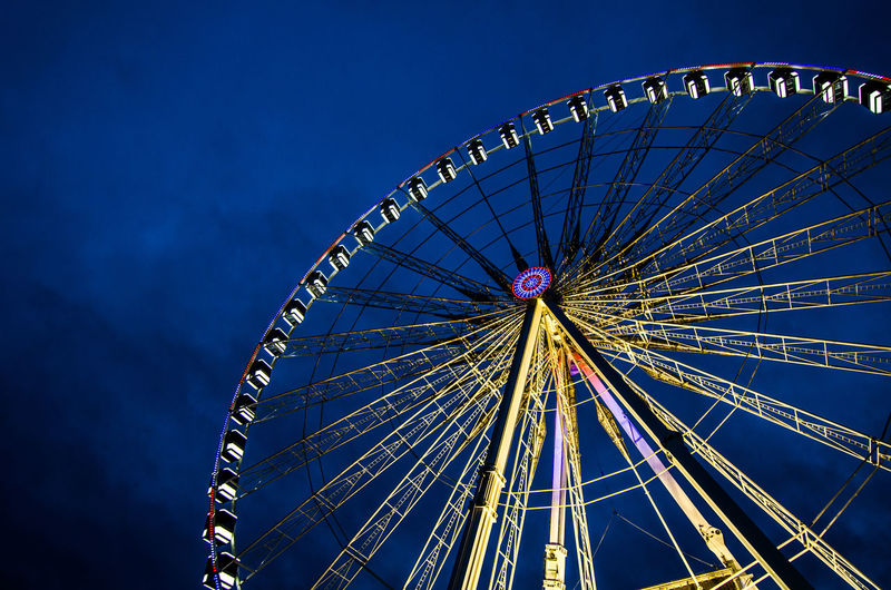 Spinning wheel at night Amusement Park Arts Culture And Entertainment Ferris Wheel Low Angle View Amusement Park Ride No People Night Sky Clear Sky Blue Outdoors evening Photography light The Traveler - 2018 EyeEm Awards HUAWEI Photo Award: After Dark #urbanana: The Urban Playground