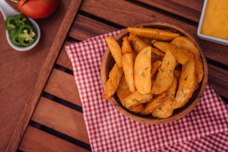 High angle view of fried potatoes in bowl on wooden table