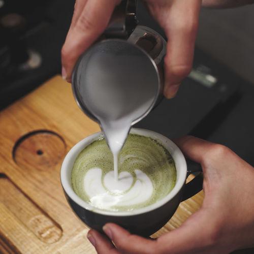 Copped hand making pattern on matcha latte