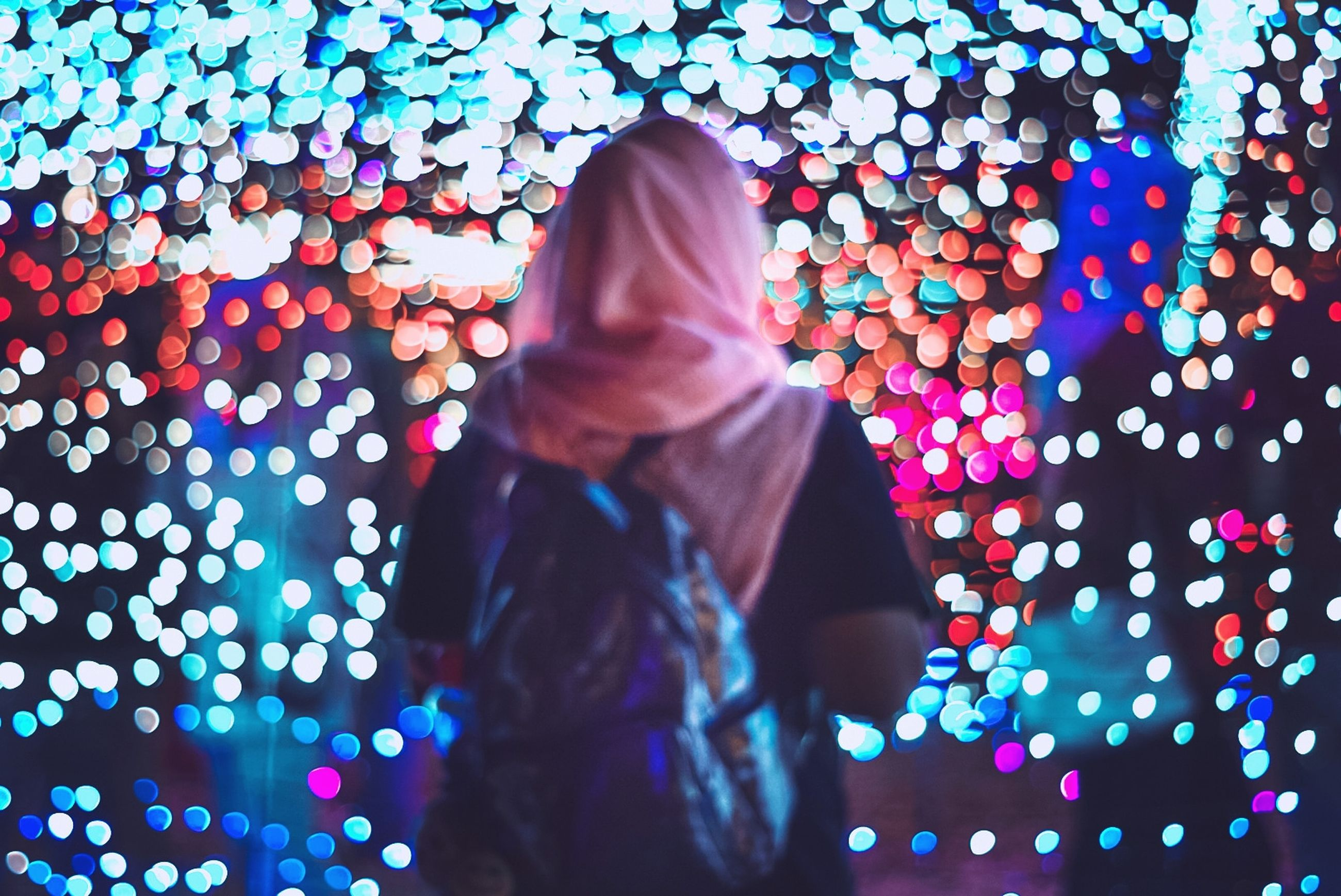 real people, illuminated, lifestyles, one person, leisure activity, multi colored, standing, women, lighting equipment, three quarter length, decoration, adult, pattern, celebration, clothing, glowing, christmas lights, casual clothing, rear view, light, warm clothing