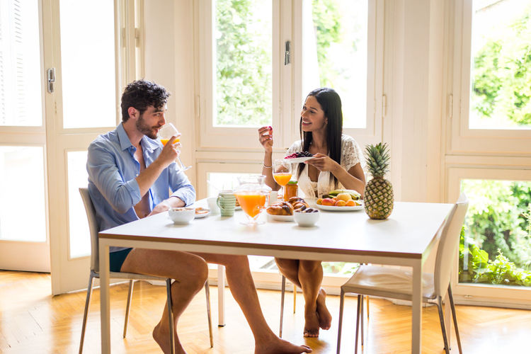 Young couple sitting on table at home