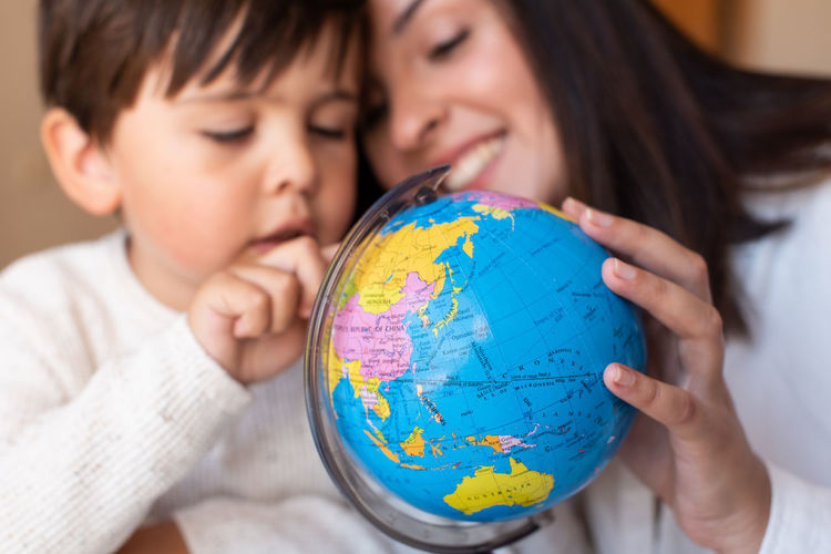 Close-up of mother and son holding globe at home