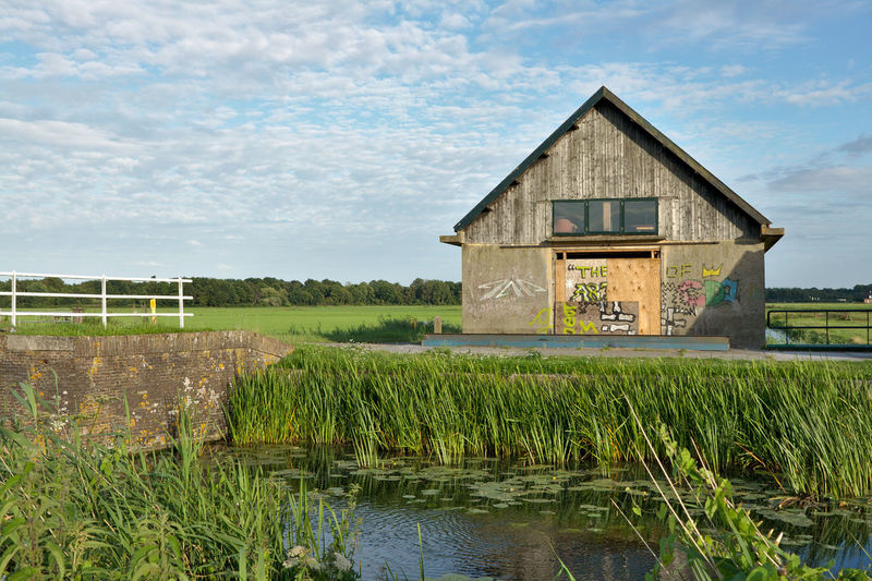Barn by grass against sky