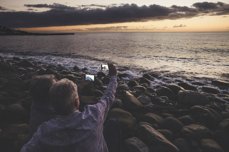 Couple taking selfie from mobile phones at beach during sunset