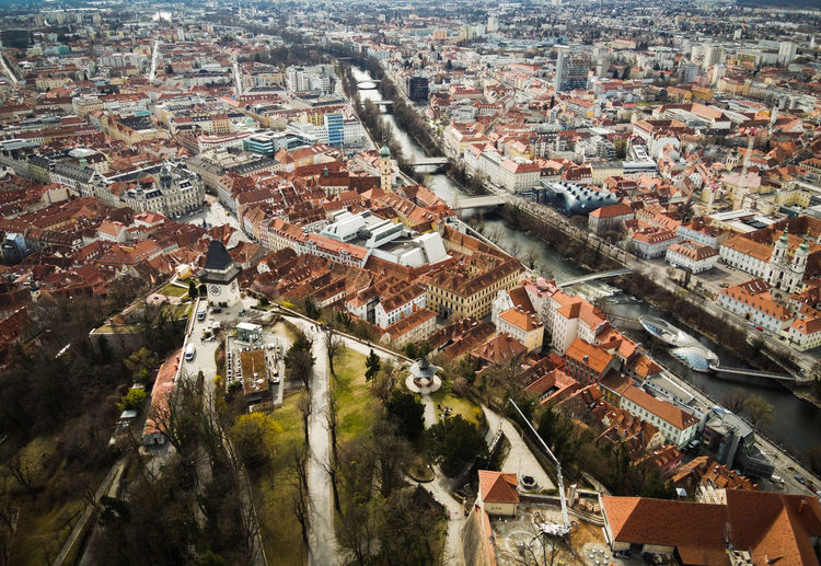 Aerial view from graz hill schlossberg in austria, cityscape with house roofs, mur river