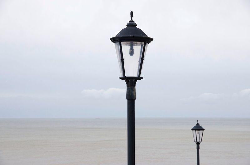 Street light by sea against sky