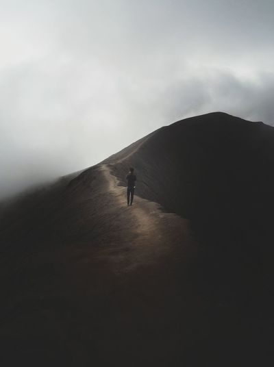 Silhouette person on mountain against sky