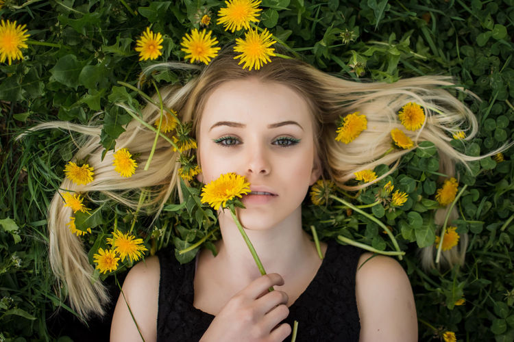 Portrait of woman with sunflower in garden