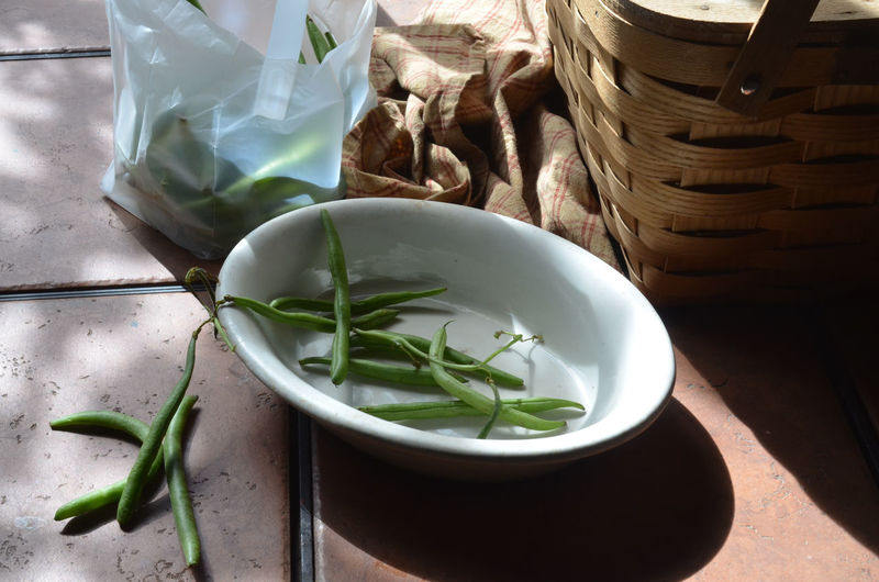 High Angle View Of Green Beans By Wicker Basket On Table