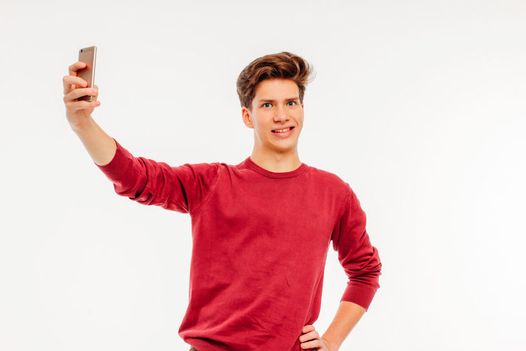 Portrait of smiling young man using phone against white background