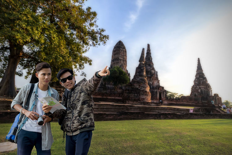 Young couple standing at temple against sky