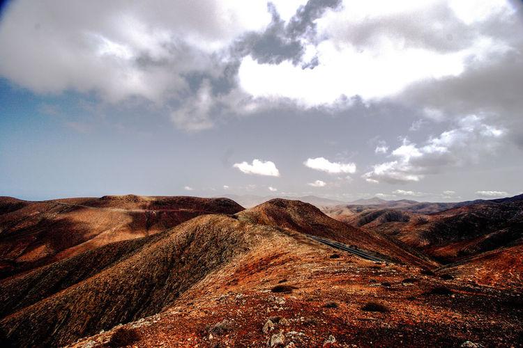 Fuerteventura, Spain. Fuerteventura SPAIN Arid Climate Beauty In Nature Cloud - Sky Day Environment Field Idyllic Island Land Landscape Mountain Mountain Range Nature No People Non-urban Scene Outdoors Remote Rock Scenics - Nature Sky Tranquil Scene Tranquility