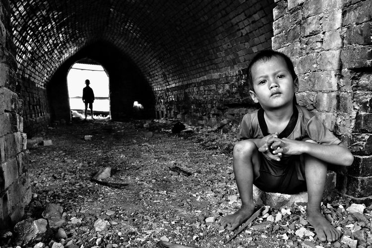 Portrait Of Boy Sitting Against Brick Wall With Brother Standing In Background