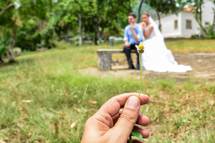 Wed Couple On Grassland With Hand Holding Flower In Foreground