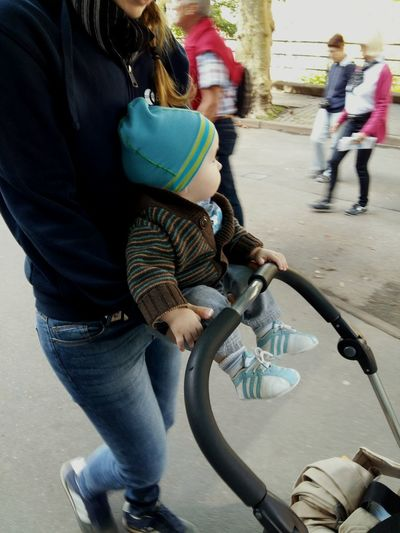 Baby boy pushes his stroller Urban Lifestyle Baby Aunt  People Out Of Focus Peoplephotography Citylife Street Photography Street Style