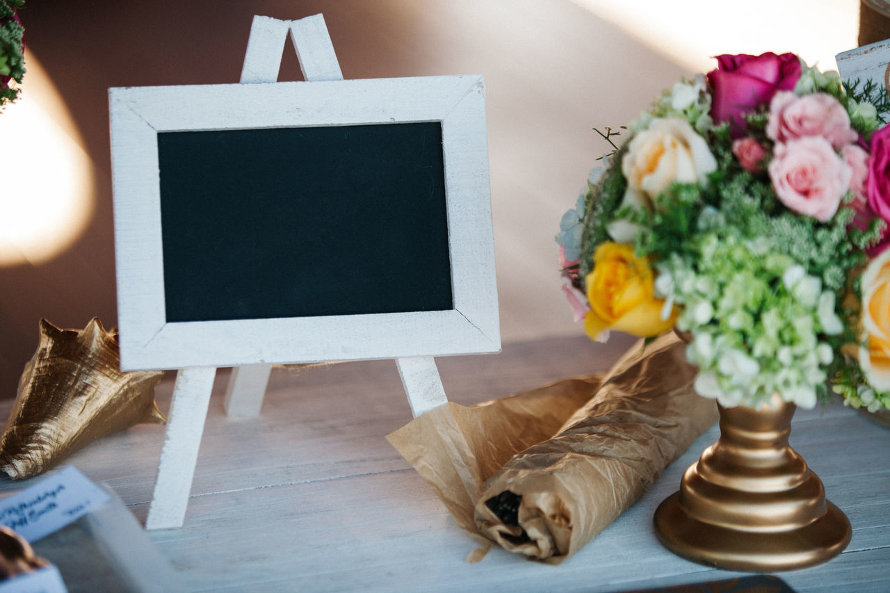 Close-Up Of Flowers By Blank Picture Frame On Table