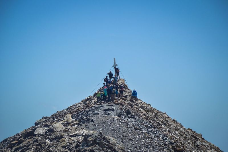 Low angle view of people on rock against clear blue sky