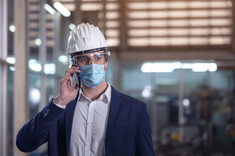 Mechanical worker with mask talking on the phone in a factory person