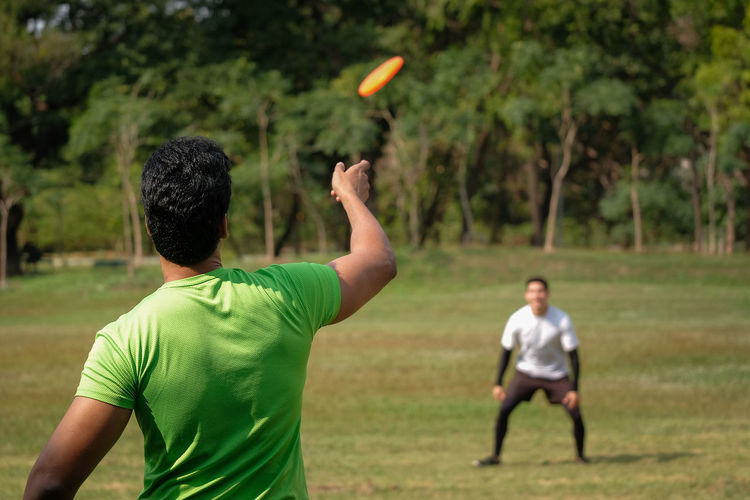 Rear view of men playing on field
