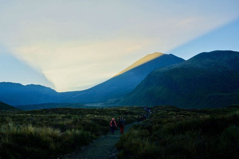 Rear view of people walking on mountain against sky on a sunrise