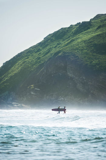 Man and woman holding surfboard in sea against mountain